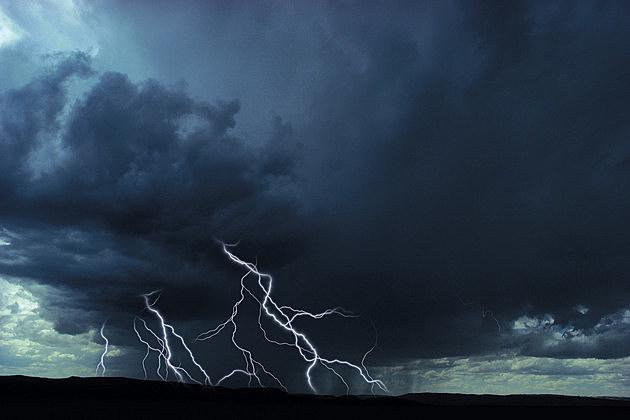 Multiple lightning bolts over rural landscape